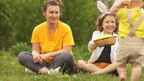 Toddler in the park throws an Easter egg. Mom has a surprised face. Happy easter family stock footage