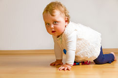 Toddler on a parquet floor Royalty Free Stock Image
