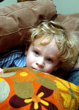Toddler peaking from pillows stock images