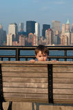 Toddler Peek A Boo. An adorable girl toddler playing peek a boo against a downtown New York City background royalty free stock images