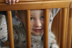 Toddler Peeking Through Crib Stock Photos