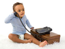 Toddler on the phone. Adorable little 18 month old toddler boy of African decent playing with a telephone Royalty Free Stock Photo