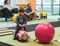 Toddler on pink car. Swarzedz, Poland - January 13, 2019: Toddler boy sitting on a pink toy car next to a ball in the Hola indoor playground royalty free stock photography