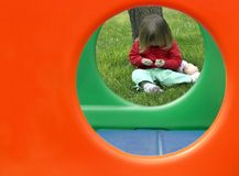 Toddler with Play Structure. Small child framed by holes in play structure Stock Image