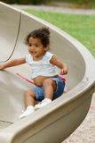 Toddler on playground slide. A view of a cute little 2-year old toddler playing outside on a playground slide Royalty Free Stock Image