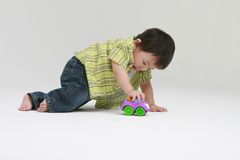 Toddler Playing. A cute toddler playing with a toy truck Royalty Free Stock Images