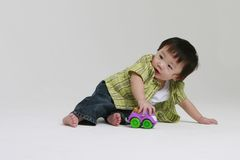 Toddler Playing. A cute toddler playing with a toy truck Stock Photography