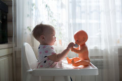 Toddler playing with baby doll singing doll out of the cup,in re Royalty Free Stock Image