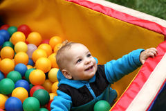 Toddler in box of balls stock photo