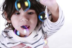 Toddler playing with bubbles Stock Images