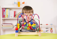 Toddler playing with a challenging toy. A stock photo of a child playing with a challenging toy in the play room Stock Photos