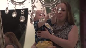 Toddler playing with chandelier stock footage