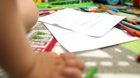 Toddler playing with colors and glue. Inside playroom with selective focus stock video footage