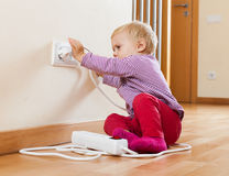 Toddler playing with electrical extension. On floor at home Royalty Free Stock Photo