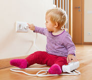 Toddler playing with extension cord and outlet Stock Photo