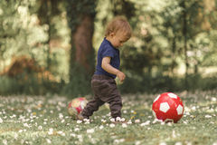 Toddler playing with football in the grass Royalty Free Stock Image