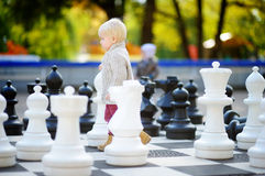 Toddler playing giant chess outdoors Stock Photos