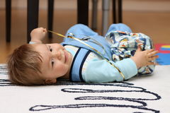 Toddler playing with gift packed in paper. While laying on his back Royalty Free Stock Photo