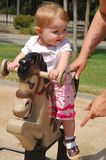 Toddler playing on horse tetter-totter Stock Image