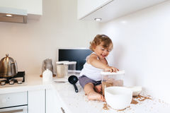 Toddler playing at the kitchen Stock Image