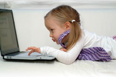 Toddler playing on laptop Stock Images