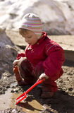 Toddler playing in mud. Toddler (2 years old) enjoying the melting snow and muddy water of spring Royalty Free Stock Photography