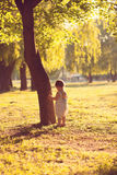 Toddler playing near the tree Stock Images