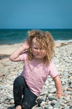 Toddler playing on a pebbled beach Stock Photography