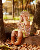 Toddler playing peek-a-boo outside on rock. Little girl playing peek-a-boo outside Stock Photography