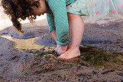 Toddler playing in puddle