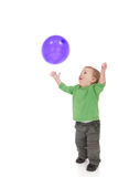 Toddler playing with purple balloon. Young toddler boy throwing and catching purple balloon. Isolated on white Stock Photo