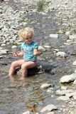 Toddler playing in river. Blonde hair toddler playing with rocks in Doftana river, Romania Royalty Free Stock Images