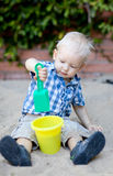 Toddler playing in sandbox. Adorable toddler playing with shovel and bucket in the sandbox Royalty Free Stock Images