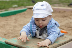 Toddler playing in sandbox Stock Images