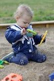 Toddler playing in sandbox. Toddler playing in a sandbox at playground Stock Photos