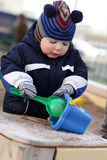 Toddler playing with shovel and bucket Royalty Free Stock Photos