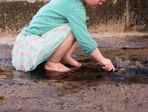 Toddler playing with stick in water Royalty Free Stock Photo