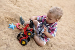 Toddler playing with toy bulldozer Royalty Free Stock Image