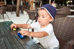 Toddler playing with toy cars Stock Images