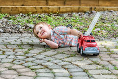 Toddler Playing with a Toy Fire Truck Outside - Series 7 Stock Photo