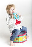 Toddler is playing with toy musical instruments  on white Royalty Free Stock Images