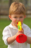 Toddler playing with toy trumpet Royalty Free Stock Photos