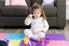 Toddler Playing With Toys At Home. Full length of adorable girl pretending to have food during tea party stock photos