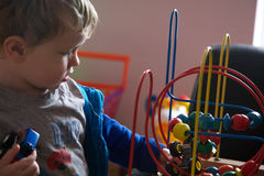 Toddler playing with toys. Portrait of small blond boy holding a toy car in one hand and moving colored objects around a wire framed loop with the other stock photography