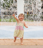 Toddler playing with water. Young girl playing with water, getting wet running happy Stock Images