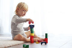 Toddler playing with wooden blocks Stock Images
