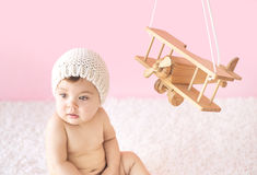 Toddler playing with a wooden plane Royalty Free Stock Photos