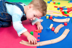 Toddler playing with a wooden train Stock Photo