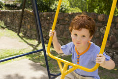 Toddler playing on yellow swing Royalty Free Stock Photos