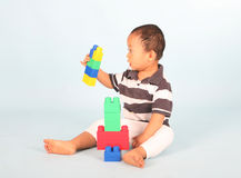 Toddler plays block. Cute toddler playing with his blocks shot over blue background Stock Photo